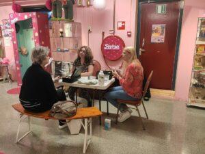 Armel Rood zit met Barbie liefhebbers aan tafel om Barbie's te taxeren.